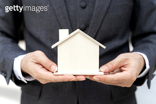 Close up asian business man holding Model house - business finance concept