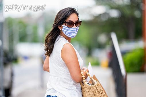 Hispanic woman shopping downtown wearing a protective mask