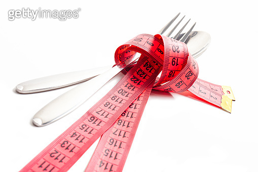 Steel spoon, fork and measuring tape on white background.