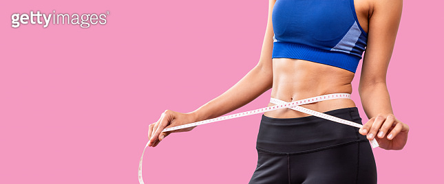 Attractive female woman torso with measuring tape on pink background, weight loss and dieting concept