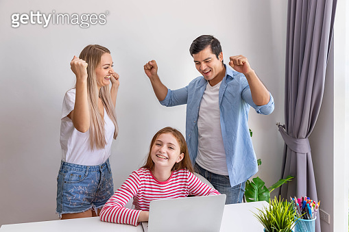 Parent father and mother watching and teaching daughter to use notebook computer at home, raise hand with cheerful, looking at camera