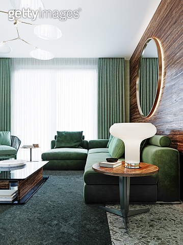 Fashionable corner sofa in green on the background of a wooden wall with a backlit mirror.