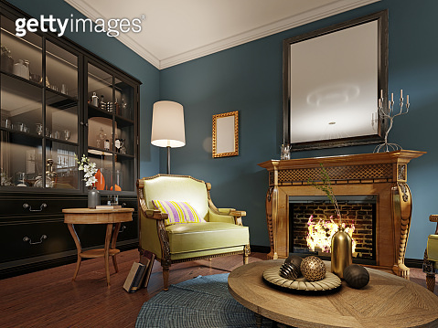 Luxurious designer chair with wooden legs and leather green leather with multi-colored pillow. Classic armchair by the wooden fireplace.