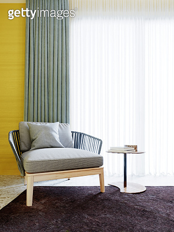 Designer fashionable white armchair with wicker armrests and wooden legs, light blue curtains, yellow walls and a brown carpet.