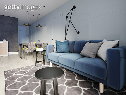 Nordic design living room with a modern blue sofa and black side tables with decor. Scandinavian contemporary style. Design hinged wall lamp.