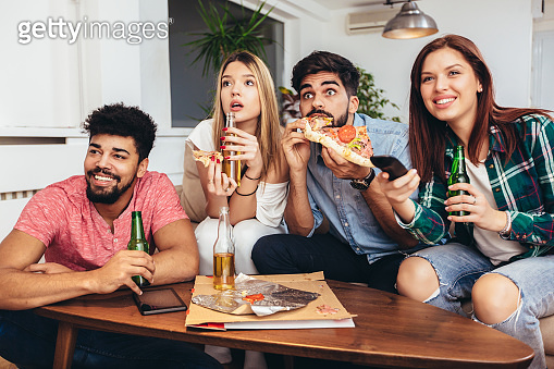 Friends eating pizza, drinking beer and watching tv.
