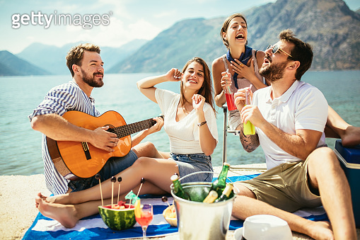 Young people having fun on summer vacation.Happy friends drinking tropical cocktails on the beach.