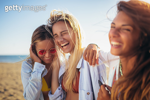 Three friends walking on the beach and laughing on a summer day, enjoying vacation.
