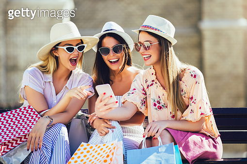 Three girls with colorful shopping bags using smart phones