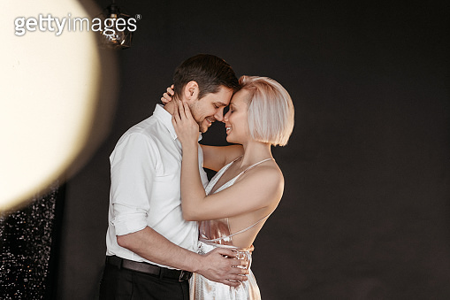 Beautiful happy couple young family in evening dresses kissing on dark background