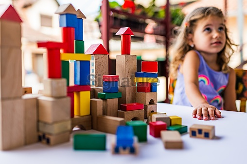 Happy little girl playing with colorful building blocks