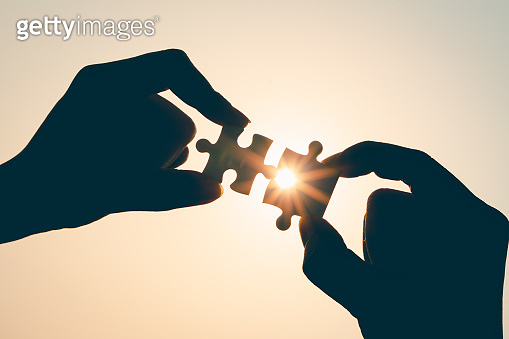 Silhouette of closeup woman and man hand connecting a piece of jigsaw puzzle over sunlight effect. symbol of association and connection concept. business strategy.