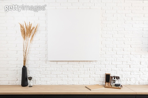 large white brick wall and canvas fragment in the center with place for text. Wooden table with set of the mans luxury multifunction accessories holder, hourglass and black vase of decorative reeds.