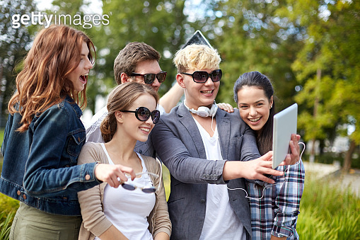 students or teenagers tablet computer taking selfie at park