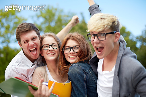 group of happy students showing triumph gesture