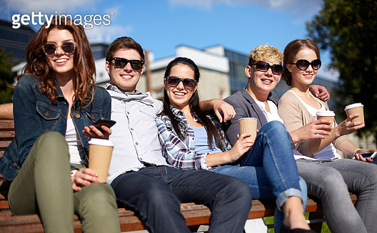 group of happy teenage students or friends drinking coffee