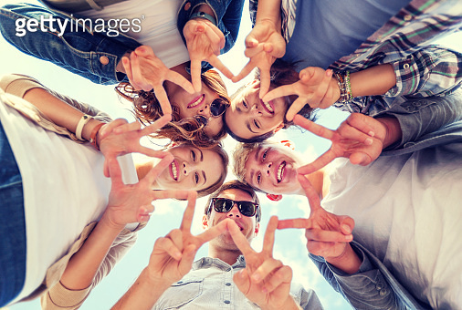 group of teenage friends showing peace or victory gesture