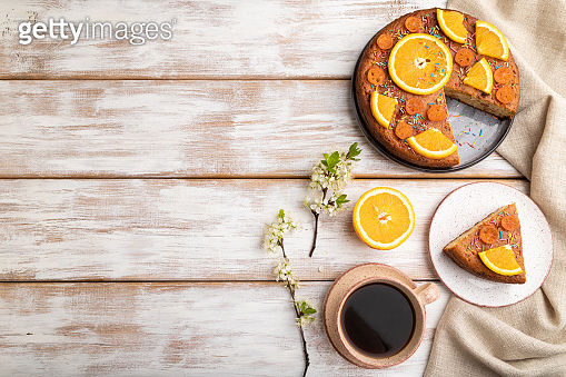 Orange cake and a cup of coffee on a white wooden background and linen textile. Top view, flat lay, copy space.
