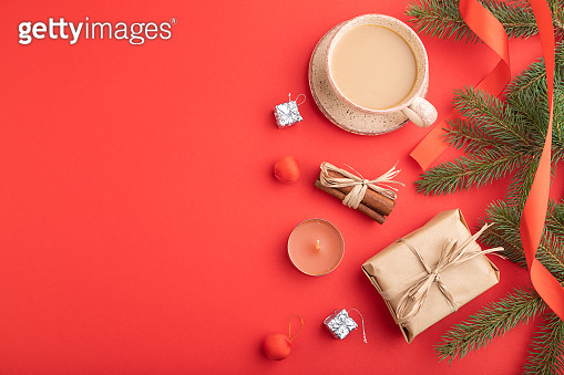 Christmas or New Year composition. Decorations, box, cinnamon, fir and spruce branches, cup of coffee, on a red paper background. Top view, copy space, flat lay.
