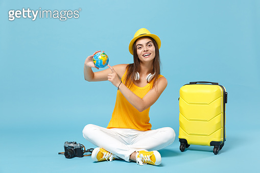 Traveler tourist woman in yellow casual clothes, hat with suitcase photo camera isolated on blue background. Female passenger traveling abroad to travel on weekends getaway. Air flight journey concept
