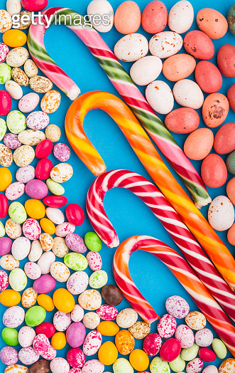 Colorful multicolored candies on a blue background. Christmas cane, chocolate eggs, caramel dragees. top view, flat lay, close up.