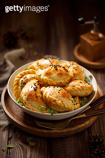 Baked dumplings (pierogi) with mushroom stuffing in a ceramic bowl on a wooden table
