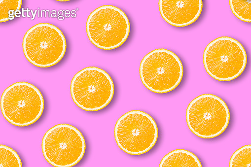 Seamless pattern of juicy orange slices on a pink background. Flat lay top view.