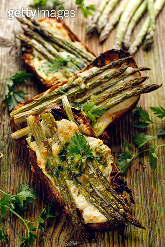 Grilled Toasts with sourdough bread with green asparagus and cheese on a wooden rustic table top view