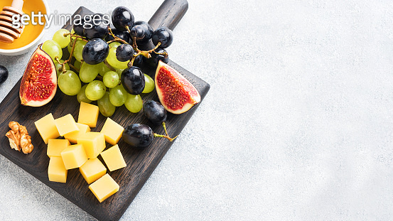 Concept of autumn appetizers. Cheese grapes figs and honey.