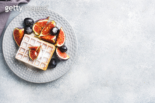 Traditional Belgian waffles with powdered sugar grapes and figs. Cozy homemade Breakfast. Gray concrete background. Copy space.