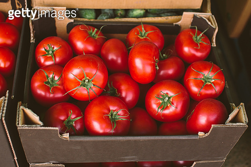 Fresh ripe tomatoes packaged in carton box on street market or greengrocery