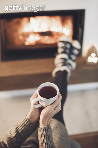 Woman relaxing near the fireplace with cup of tea, enjoying life at home