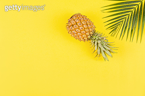 Pineapples and tropical palm leaves on yellow background. Top view, mockup, template, overhead. Summer concept. Creative flat lay with copy space