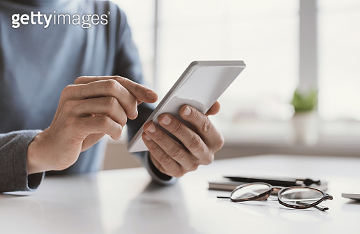 Man using smartphone in office close-up