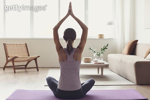 Young woman practicing yoga, meditating at home