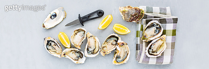 Fresh opened Oysters close-up on gray background with sliced lemon and ice. Healthy sea food. Gourmet food. Flat lay, top view, mockup, overhead, template with copy space. Online order and food delivery