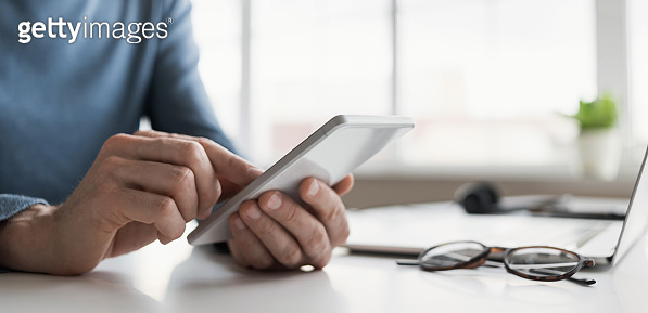 Man using smartphone, working in office close-up