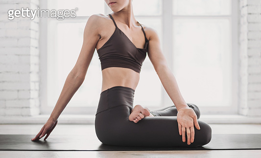 Young woman meditating and practicing yoga at home