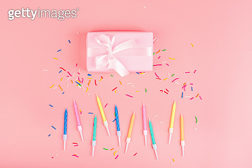 Happy birthday gift box, candles and confetti on pink background, top view. Flat lay style. Mockup, template