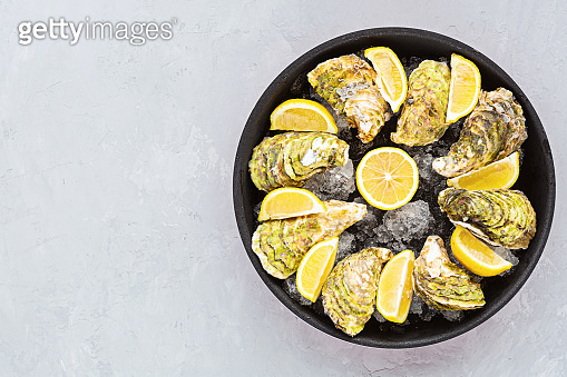 Fresh opened Oysters close-up on black plate with sliced lemon and ice. Healthy sea food. Gourmet food. Flat lay, top view, mockup, overhead, template with copy space. Online order and food delivery