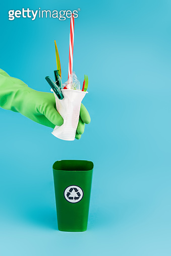 cropped view of cleaner in rubber glove throwing plastic rubbish in recycling bin on blue background, panoramic shot