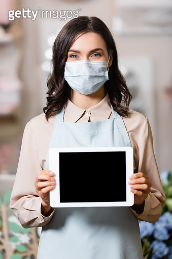 florist in medical mask holding tablet with blank screen while looking at camera
