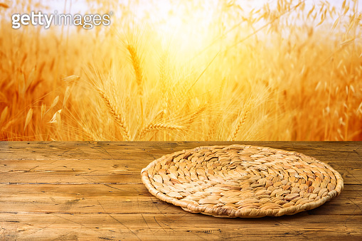 Empty wooden table with wicker round placemat over wheat field background. Harvest mock up background