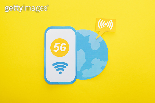 top view of 5g lettering on paper smartphone near globe on yellow background