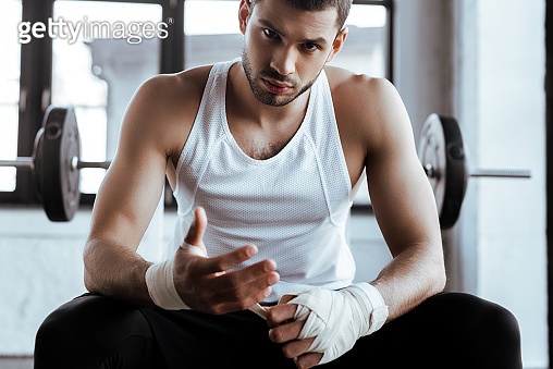 handsome sportsman wrapping hand in sports bandage and looking at camera