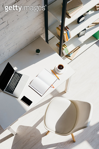 top view of home office with laptop, smartphone and cup of coffee in sunlight
