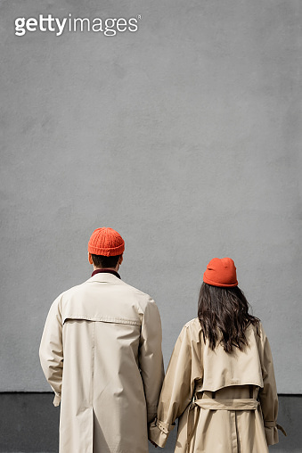 back view of couple in trench coats and hats standing near grey wall