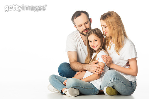 happy family sitting on floor with crossed legs and embracing isolated on white