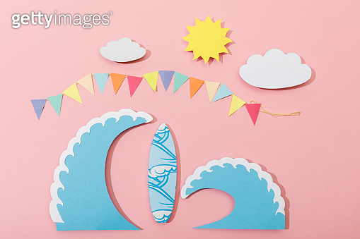 Top view of paper cut sun, clouds, flags, surfboard and sea waves on pink background