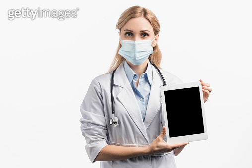 nurse in medical mask and white coat holding digital tablet with blank screen isolated on white